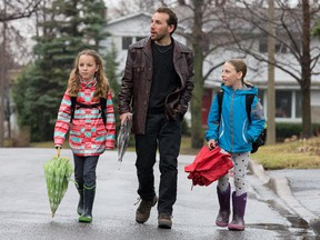 Dan Rubinstein, author of the book Born to Walk, walked all over the world researching his book. But he was struck by a car while walking his children, Daisy, (L) and Maggie, (R), both 10, to school in his Alta Vista neighbourhood. Assignment - 120364 Photo taken at 08:25 on April 21. (Wayne Cuddington / Ottawa Citizen)