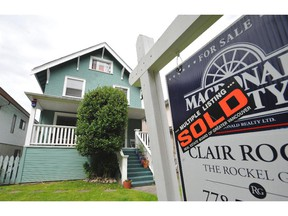 A house sports a For Sale/Sold sign in Vancouver, B.C., June 21, 2012.
