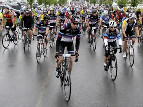 Participants depart the EY Centre at the start of the Ride the Rideau cycling event in Ottawa on Saturday, September 6, 2014. More than 900 riders braved the rain to participate in the ride, with proceeds benefiting cancer research at the Ottawa Hospital.