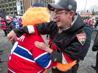 Senators fan Hugo Lamarche gets tackled by Youppie at FanJam 2015 as the Ottawa Senators get set to take on the Montreal Canadiens at the Bell Centre in Montreal for Game 5 of the NHL Conference playoffs on Friday evening.