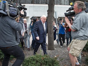 Suspended Sen. Mike Duffy makes his through the bushes and around the media as he heads to a waiting vehicle following the early conclusion of his trial at the Elgin Street Courthouse on April 13, 2015.