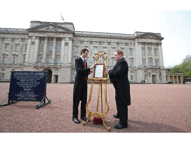 Members of the British Royal household place a bulletin announcing that Catherine, Duchess of Cambridge, Prince William's wife, has given birth to a baby girl, on an easel on the forecourt of Buckingham Palace in London on May 2, 2015. Prince William's wife Kate gave birth to a girl on Saturday, sparking celebrations for the royal couple's new arrival, a princess who becomes the fourth in line to the British throne.