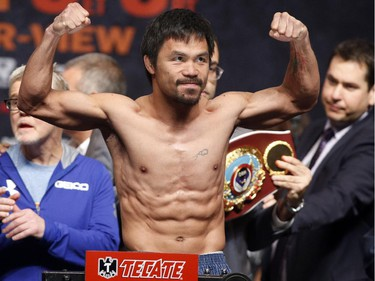 """Manny Pacquiao gestures while standing on the scale for the weigh-in on May 1, 2015 in Las Vegas, Nevada one day before their """"Fight of the Century"""" on May 2 at the MGM Grand Garden Arena."""