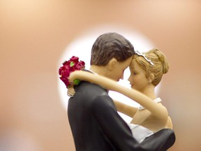 Figurines of a bride and a groom sit atop a wedding cake.