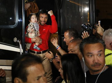 Boxer Manny Pacquiao, of the Philippines, holds his youngest child, Israel, as they arrive at the Delano Las Vegas hotel Monday, April 27, 2015, in Las Vegas. Pacquiao is scheduled to fight Floyd Mayweather Jr. in a welterweight boxing match in Las Vegas Saturday.
