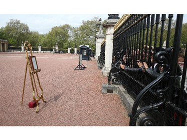LONDON, ENGLAND - MAY 2:  Crowds gather as an easel is placed in the forecourt of Buckingham Palace following the announcement that Catherine, Duchess of Cambridge has given birth to a baby girl at St Mary's Hospital on May 2, 2015 in London, England. The Duchess was safely delivered of a daughter at 8:34am this morning, weighing 8lbs 3 oz who will be fourth in line to the throne.