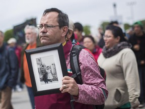 The Truth and Reconciliation march took place in Gatineau making its was into Ottawa, May 31, 2015. John Moses hold a photo of his father Russ and aunt Thelma taken at the Mohawk Institute in 1943.