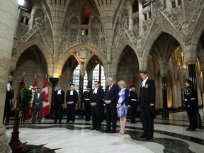 Prime Minister Stephen Harper, his wife, Laureen, along with House of Commons Speaker Andrew Scheer, and members of the Commons staff and family members impacted by acts terror, stand for a moment of silence during a wreath laying ceremony marking the National Day of Remembrance for Victims of Terrorism in the Hall of Honour on Parliament Hill.