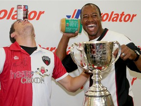 Ottawa Redblacks quarterback, Henry Burris (right), and Ottawa Fury defender, Mason Trafford, wound up with cans of soup and peanut butter jars in front of the Grey Cup at the Ottawa Food Bank Thursday, July 16, 2015. Both teams are asking fans to bring a non perishable food item or money donation to their games this weekend in the hopes of raising 55,000 pounds of food for the Ottawa Food Bank.