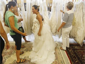 Anick Langlais. center, searches for a wedding dress during the McCaffrey bankruptcy sale at in Ottawa Thursday August 20, 2015.  Langlais lined up at 6:30 a.m. to get a chance to find the perfect dress. The sale runs until Sunday or until the last dress is sold.