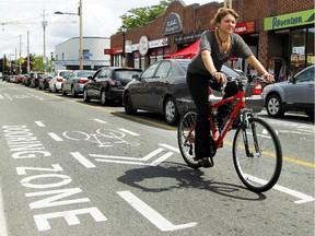 A cyclist is seen passing through the 'dooring zone' on Wellingston street on Saturday, Aug. 8, 2015.
