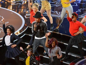 "Pharrell Williams, center, performs ""Happy"" during the Oscars at the Dolby Theatre on Sunday, March 2, 2014, in Los Angeles."