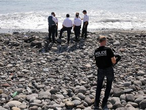 Police officers inspect metallic debris found on a beach in Saint-Denis on the French Reunion Island in the Indian Ocean on August 2, 2015, close to where where a Boeing 777 wing part believed to belong to missing flight MH370 washed up last week.