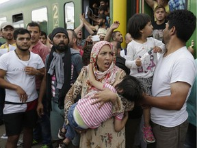 A woman carrying a child stands outside a train with migrants that was stopped in Bicske, Hungary, Thursday, Sept. 3, 2015. More than 150,000 migrants have reached Hungary this year, most coming through the southern border with Serbia. Many apply for asylum but quickly try to leave for richer EU countries.