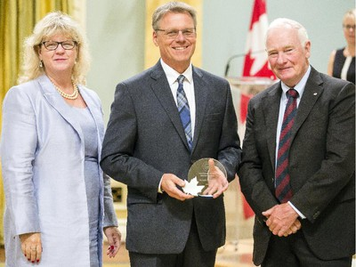 Jacques Paquette from Employment and Social Development Canada, center, receives the Public Service Award of Excellence, The Joan Atkinson Award, from Janice Charette, clerk of the privy council, left, and David Johnston, Governor General of Canada, right, at Rideau Hall Wednesday September 16, 2015. (Darren Brown/Ottawa Citizen) - Assignment 121627