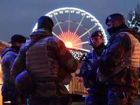 Belgian soldiers patrol during the opening night of the annual Christmas market on November 27, 2015 in Brussels. Belgium reduced the terrorism alert in Brussels from its highest possible level on November 26 after Prime Minister Charles Michel said the threat of a Paris-style jihadist attack was no longer as imminent.