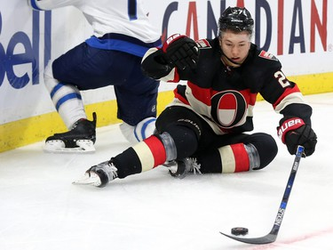 Curtis Lazar of the Ottawa Senators collides with Ben Chiarot of the Winnipeg Jets during first period NHL action.