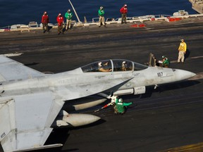 "Flight deck personnel perform prelaunch checks on an F/A-18F Super Hornet, attached to the ""Checkmates"" of Strike Fighter Squadron Two One One (VFA-211), on the flight deck of the nuclear-powered aircraft carrier USS Enterprise (CVN-65). Enterprise and embarked Carrier Air Wing One (CVW-1) are currently underway on a scheduled six-month deployment. U.S. Navy Photo by Mass Communication Specialist Seaman Apprentice Tracey L. Whitley. Image released by LT Mark C. Jones, PAO CVN 65."