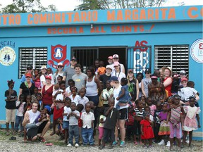In the most recent Dominican trip, Mark Podgorski (in back with the blue ball cap), All Saints students and Dominican students pose outside a school built with funds raised by the Ottawa high school.