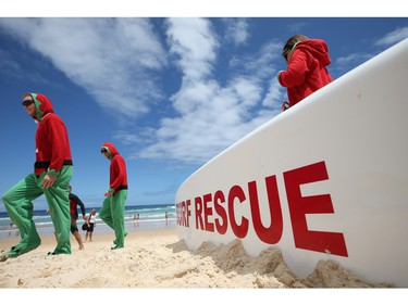 James Conaghan, left, of Australia in Santa's elves costume, walks past a surf rescue board on Bondi Beach with relatives from Ireland Ross and Sarah Conaghan, right, while celebrating Christmas Day in Sydney, Australia, Friday, Dec. 25, 2015.
