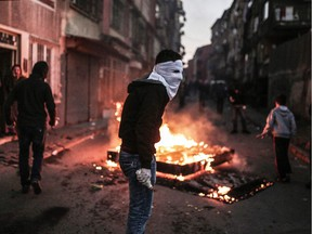 A masked protester holds a petrol bomb during clashes with Turkish police.