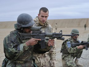 A Canadian Forces soldier is shown mentoring an Afghan National Police officer in 2011. DND photo.