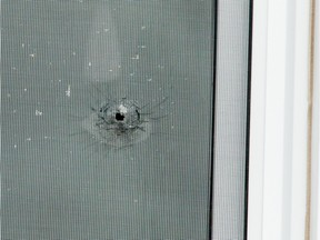 Apparent bullet hole in a second floor window of the unit on Innes Road where a man was shot in the leg as he slept.