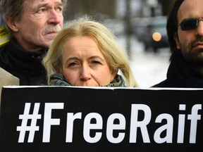 """An activist of the human rights NGO Amnesty International stands behind a banner reading """"#FreeRaif"""" as she demonstrates for the release of jailed Saudi blogger Raif Badawi in front of the embassy of Saudi Arabia in Berlin, on January 8, 2016. Badawi was sentenced to 10 years in prison and 1,000 lashes for insulting Islam.  / AFP / TOBIAS SCHWARZTOBIAS SCHWARZ/AFP/Getty Images"""