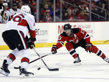 New Jersey Devils left wing Mike Cammalleri (13) competes for the puck with Ottawa Senators defenseman Patrick Wiercioch (46) during the second period.