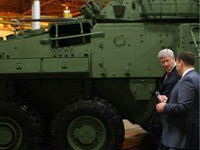 Prime Minister Stephen Harper tours the General Dynamics Land Systems - Canada plant, next to a LAV 6.0 (Light Armoured Vehicle) being built for Canada, at the facility in London, Ont., Friday, May 2, 2014.