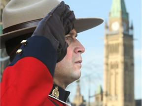 With Parliament Hill in the background, a Mountie salutes.