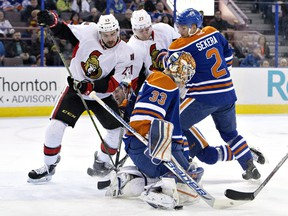 Ottawa Senators ' Nick Paul (13) and Curtis Lazar (27) battle with Edmonton Oilers' Andrej Sekera (2) as goalie Cam Talbot (33) makes the save during first period NHL action.