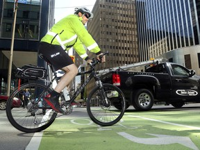 A cycling by-law officer makes his way across Laurier Avenue's bike lanes  in Ottawa, Thursday morning, May 22, 2014.