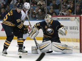 Buffalo Sabres defenceman Rasmus Ristolainen tangles with Ottawa Senators right-winger Alex Chiasson as Sabres goaltender Chad Johnson makes a save during the second period Friday, March 18, 2016, in Buffalo.
