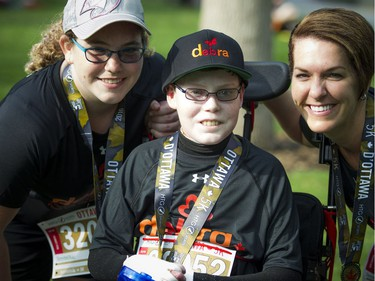Jonathan Pitre, centre, with his sister Noemy and mother Tina, pose after finishing the 5K race part of Tamarack Ottawa Race Weekend Saturday May 28, 2016.