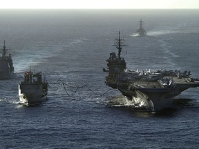 050614-N-0120R-129  The aircraft carrier USS Kitty Hawk (CV 63) receives fuel during a replenishment at sea from the Royal Australian Navy auxiliary oiler replenishment vessel HMAS Success (AOR 304) as U.S. Navy guided missile cruiser USS Cowpens (CG 63) steams alongside and guided missile destroyer USS John Paul Jones (DDG 53) trails behind, on June 14, 2005.  The ships are operating in the Coral Sea, off the coast of Australia's Queensland region, as part of Exercise Talisman Saber 2005.  Talisman Saber is a combined U.S.-Australia command post and field training exercise, demonstrating the U.S. and Australian commitment to the military alliance and regional security.  DoD photo by Petty Officer 2nd Class William H. Ramsey, U.S. Navy.  (Released)
