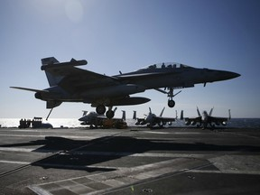 A US Navy F/A-18 Super Hornet fighter lands onto the deck of the USS Ronald Reagan, a Nimitz-class nuclear-powered aircraft carrier, during a joint naval drill between South Korea and the US in the West Sea off South Korea on October 28, 2015.