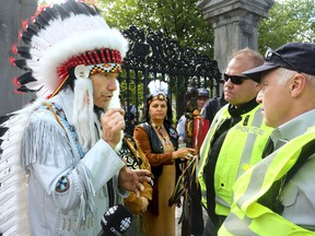 Billy Carle, grand chief of the Confederation of Aboriginal People of Canada, has a discussion with RCMP officers outside Rideau Hall on Monday, June 6, 2016.