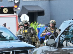 FBI, Orlando Police Department and the Orange County Sheriff's Office personnel investigate the attack at the Pulse nightclub in Orlando Fla., Sunday, June 12, 2016.