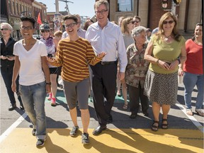 Somerset Coun. Catherine McKenney, second from left, and Mayor Jim Watson, center, help officially open the permanent rainbow crosswalks at the intersection of Somerset and Bank Streets Thursday.