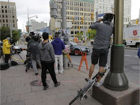 Pedestrians and news crews were clamouring into the early evening to catch glimpses of the sinkhole that opened up this morning just east of the intersection of Rideau Street and Sussex Drive, which caused a gas leak and building evacuations, on June 8, 2016. Cement trucks were just beginning to fill the hole around 6 p.m.