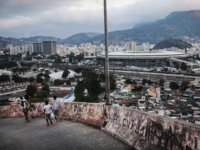 RIO DE JANEIRO, BRAZIL - JUNE 18:  People walk, with Maracana stadium in the background, in the Mangueira 'favela' community on June 18, 2016 in Rio de Janeiro, Brazil. Much of the Mangueira favela community sits about a kilometer away from Maracana stadium, which will be the site of the opening and closing ceremonies for the Rio 2016 Olympic Games. The stadium has received hundreds of millions of dollars in renovations ahead of the World Cup and Olympics. The Morar Carioca plan to urbanize Rio's favelas, or unplanned settlements, by 2020, was one key social legacy project heralded ahead of the Rio 2016 Olympic Games. The plan has mostly failed to materialize. Around 1.4 million residents, or approximately 22 percent of Rio's population, reside in favelas which often lack proper sanitation, health care, education and security due to gang and police violence.