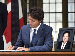 Prime Minister Justin Trudeau signs a book of condolence for Liberal MP Mauril Belanger, who died Tuesday, on Parliament Hill, Wednesday, Aug. 17, 2016 in Ottawa. Belanger, 61, who served as MP for Ottawa-Vanier since 1995, was diagnosed with ALS, also known as Lou Gehrig's disease, in November 2015.