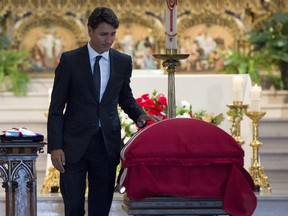 Prime Minister Justin Trudeau touches the casket of MP Mauril Belanger after delivering a eulogy during his funeral at the Notre-Dame Cathedral Basilica, on Saturday, Aug. 27, 2016 in Ottawa.