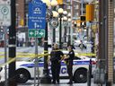 Police stand in front of businesses on Dalhousie Street in the ByWard Market after a fatal shooting in Ottawa on Sunday, August 14, 2016.