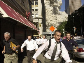 FILE - In this Sept. 11, 2001 file photo, people run from a collapsing World Trade Center tower in New York.