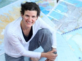 Jennifer Kingsley sits on a pile of navigational charts she used on her travels north. The Ottawa writer has teamed up with a photographer to compile a web-based project called Meet the North.