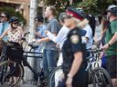 Ottawa Police and onlookers at the site where a cyclist died in a collision with a truck at Laurier Avenue and Lyon Street Thursday morning.