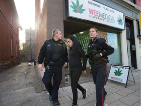 A woman is arrested and placed in a cruiser as Ottawa police conduct raids on a number of pot shops including Wee Medical on Rideau Street.