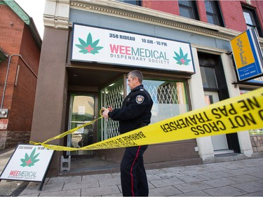 An officer places crime tape at the scene as Ottawa police conduct raids on a number of pot shops including Wee Medical on Rideau St.